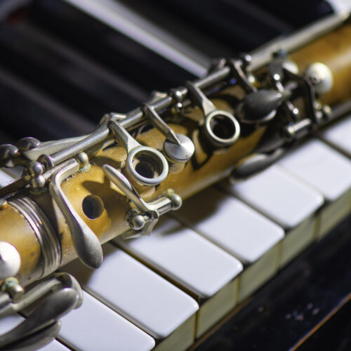 Antique clarinet leaning on piano key